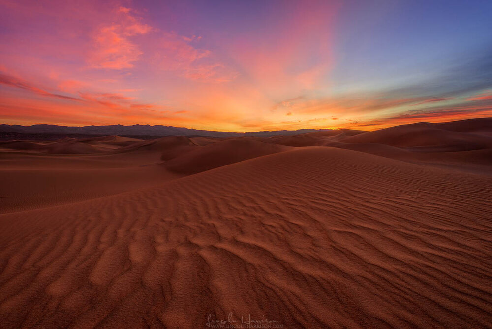 colourful sunrise oveer windswept dunes in death valley national park