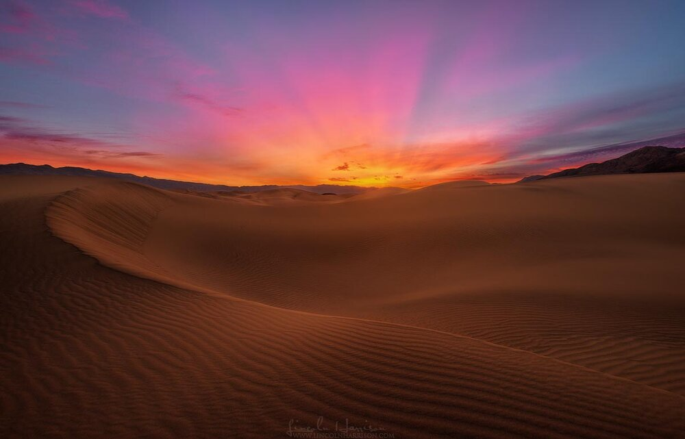 The rising sun lights up the sky over the mesquite dunes in death valley california