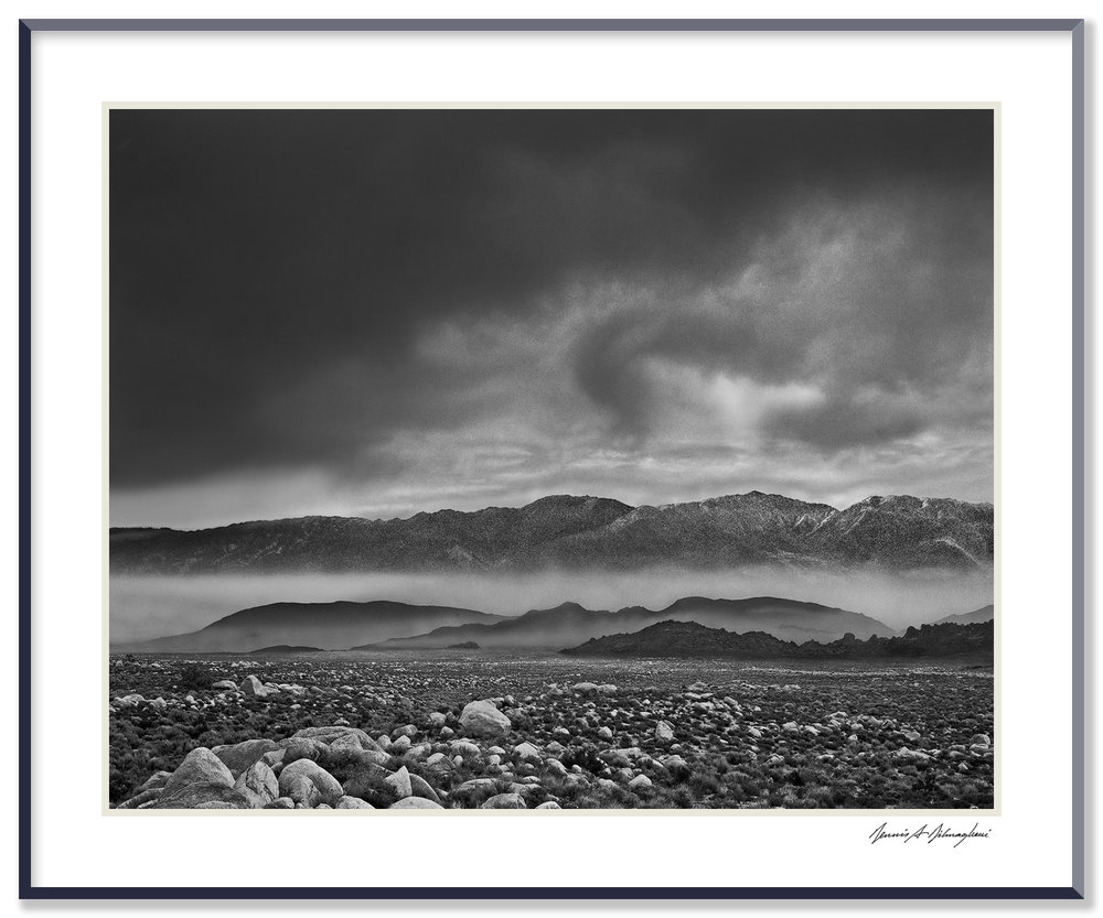 Storm – Looking toward Inyo Range - Owens Valley, Near Lone Pine, California  This portion of the Owens Valley, is an awesome sight. Millions of boulders from the formation of the Sierra range are strewn over thousands of acres. Clouds developed rapidly preceding an impending storm, while fog drifted thru the valley.