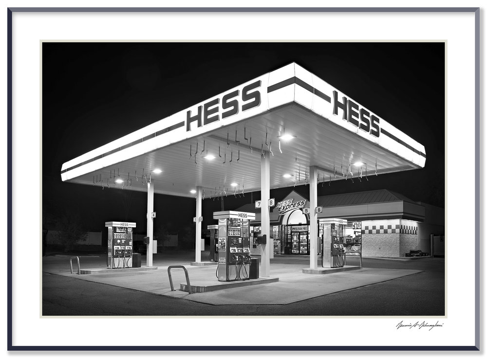 Hess Gas Station - Hudson, NY   This recent Hess Gas Station provides a wonderful contrast to the image of Mora Valley Oil Co. taken many years before. The two photographs must be appreciated side by side. Same merchandising concept, different era.  In this image the stark, monolithic structure towers over a spotless concrete pad and the emptiness gives the scene a stage like appearance.