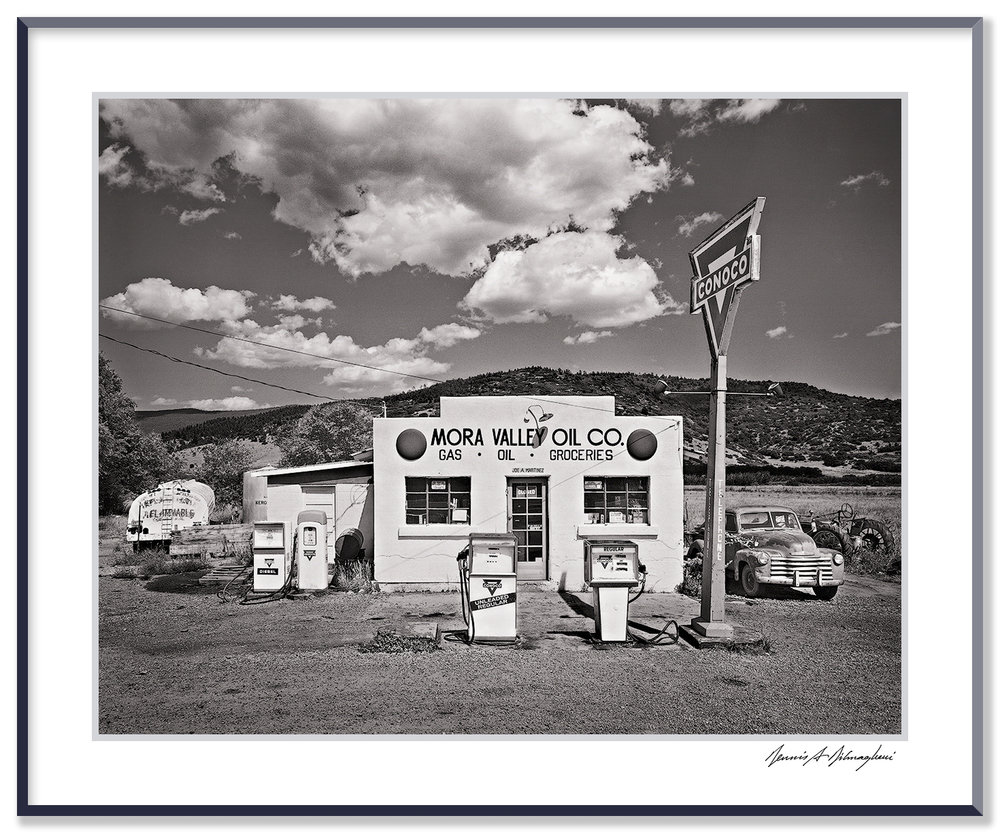 "Mora Valley Oil Company - Cleveland, New Mexico   This scene in the heart of Mora Valley, New Mexico, glowed in the early afternoon sun with down-home Americana spirit.  Vintage building, classic style gas pumps, trucks, tractor, big sky... The granddaughter of the original gas station owner found the image on the internet and wrote to me, ""Thank you for taking this photo. It brought a tear of joy to see something so dear to my family as it used to be in the ""good old days""."