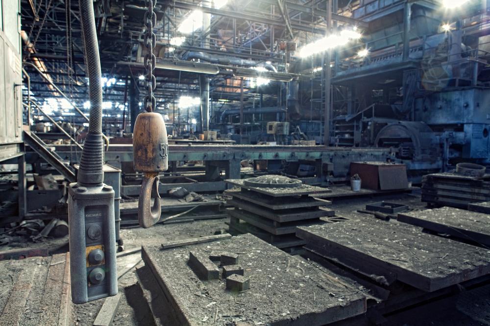 Abandoned Steelworks Ettermiddagslys skinner gjennom de små takvinduene i de støvete lokalene til et forlatt stålverk i Østerrike. Uvisst når de siste arbeiderne gikk herfra, men trær og vegetasjon har alt begynt å vokse igjennom gulv og maskiner.