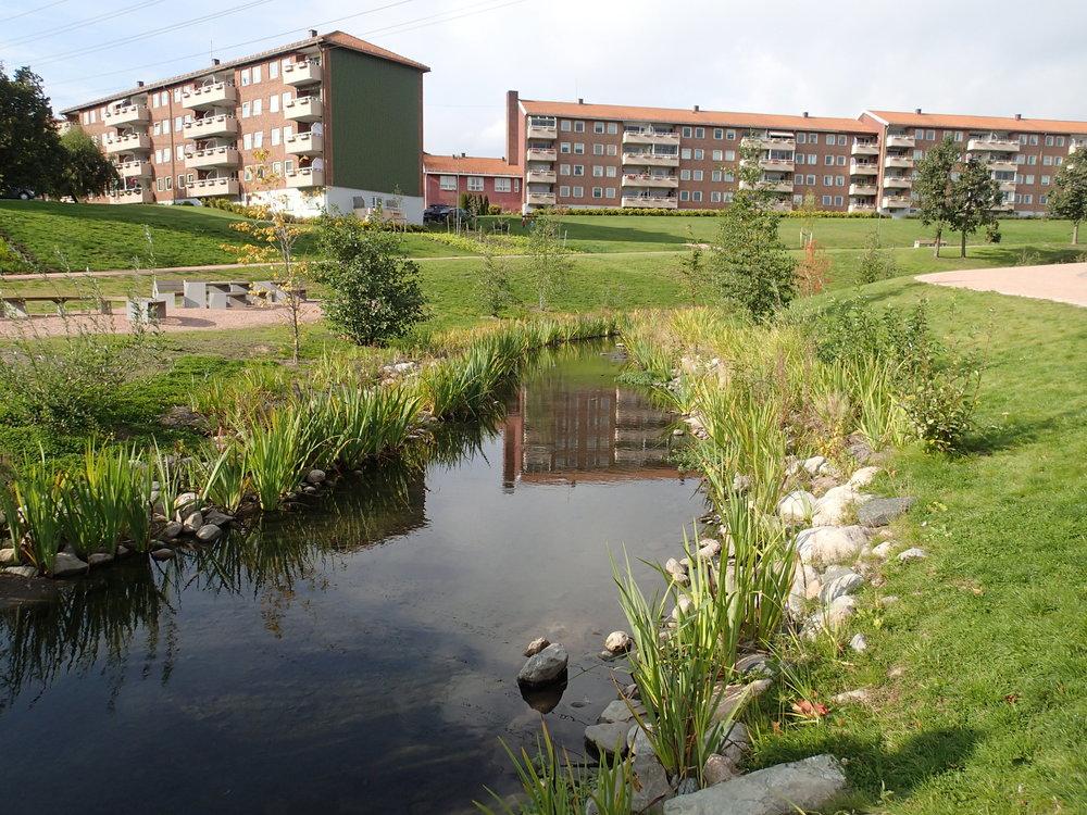 I Bjerkedalen park har åpning av Hovinbekken gikk muligheten til å etablere et vannspeil og uteområder med stor grad av variasjon og estetisk kvalitet. Parken har blitt et viktig møte- og rekreasjonsområde og vant Oslo bys arkitekturpris i 2015. Foto: Taran Aanderaa