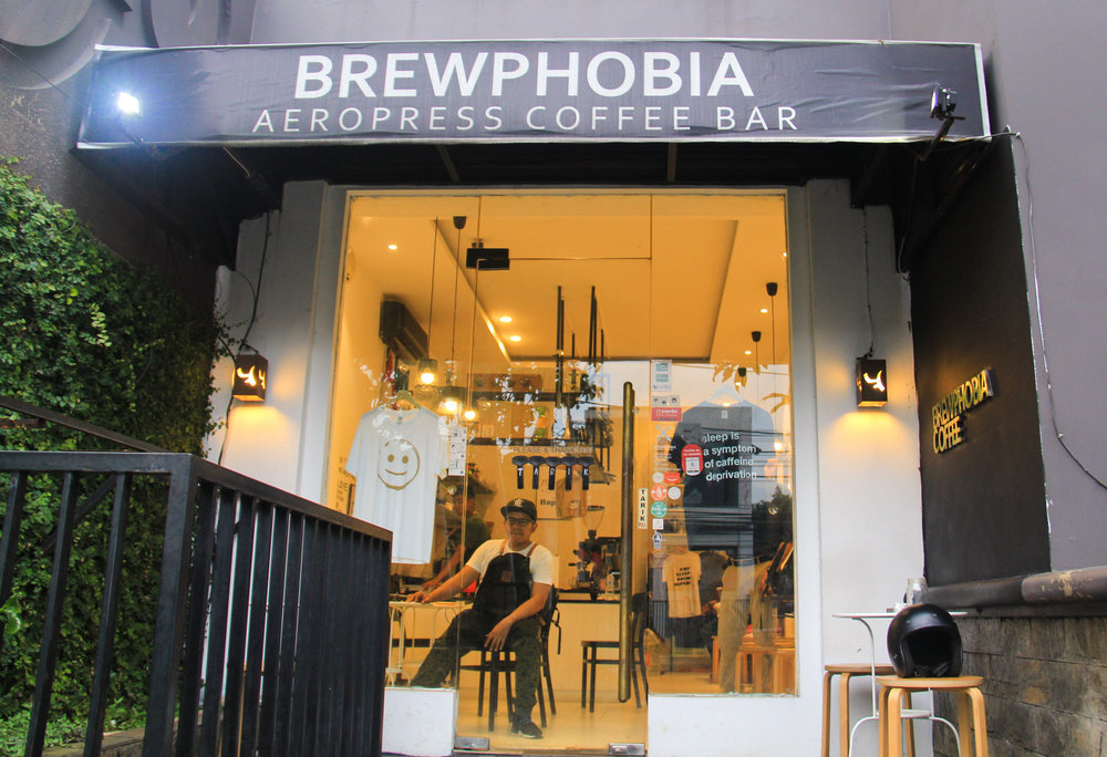 Mirza Luqman Effendy, founder of the Brewphobia coffee shop in South Jakarta, is seen through the window in his shop. Photo: Yosef Riadi for NPR