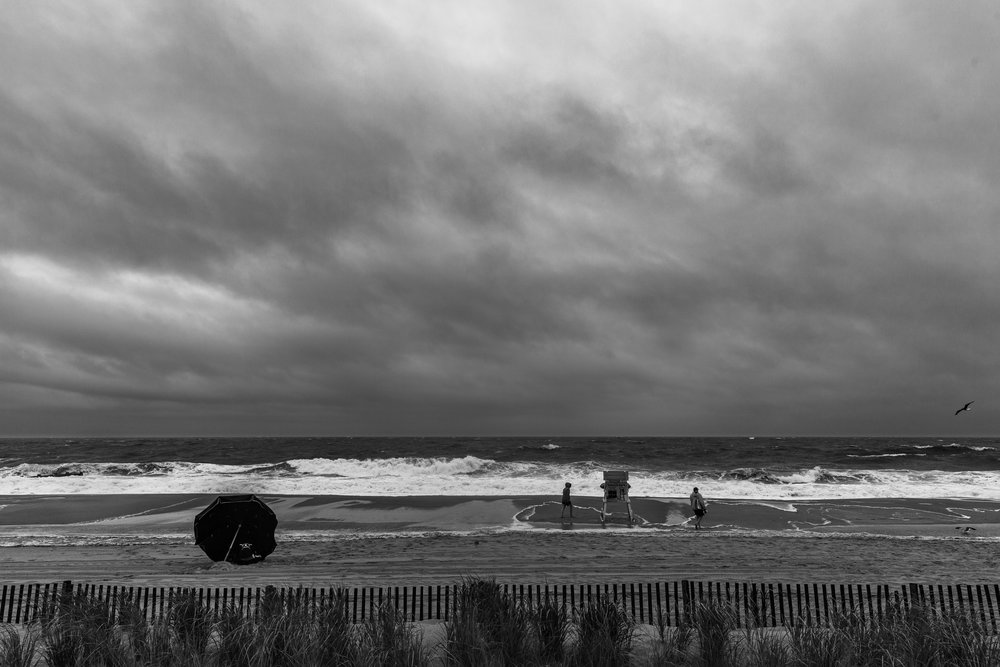 Beachgoers braving the wind, rain and surf