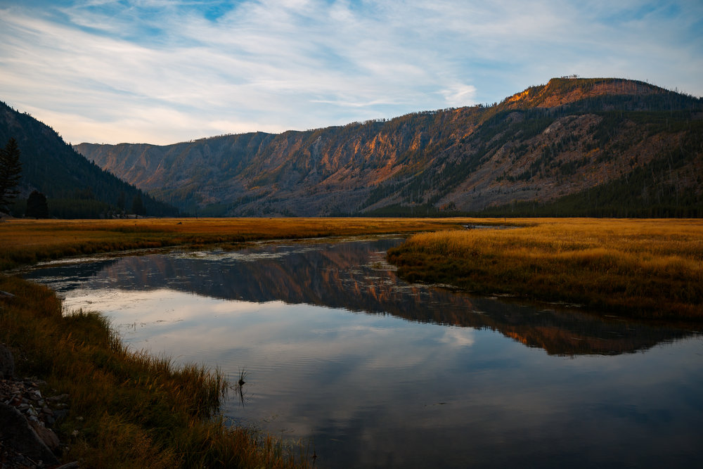 The Madison River as sunrise grazes the face of cliffs