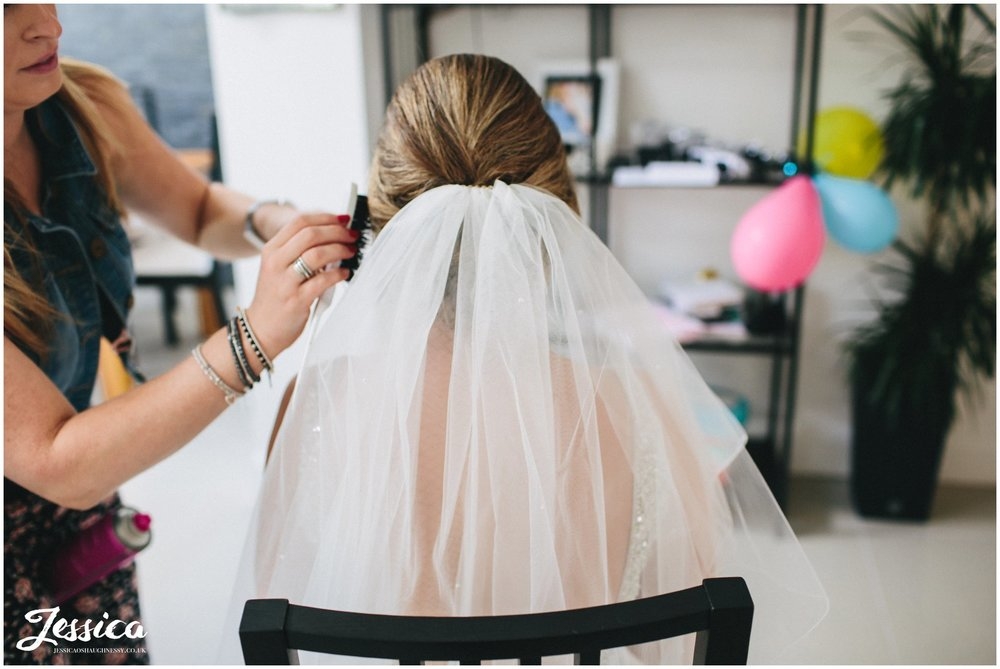 bride has her veil fitted on the morning of her wedding day