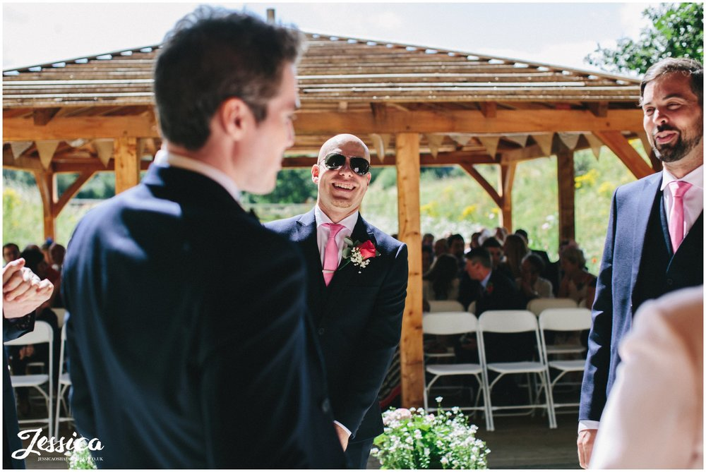 the groom laughs as he waits for his bride to arrive - tower hill barns wedding photography