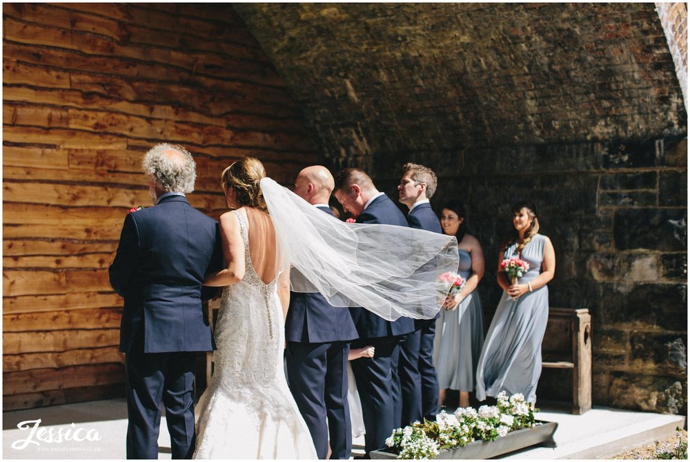 bride links arms with her father during the ceremony at her tower hill barns wedding