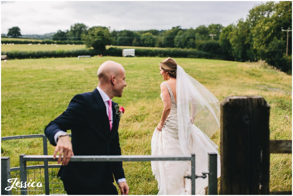 the bride & groom go wandering through the fields in north wales