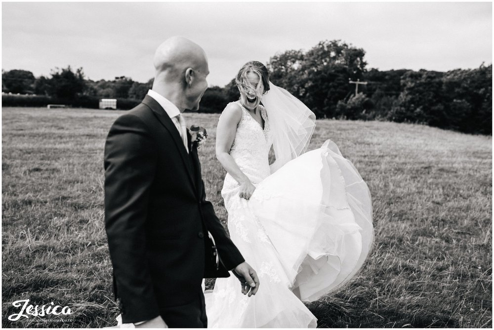 windswept bride walking through fields with her groom - tower hill barns wedding photographer