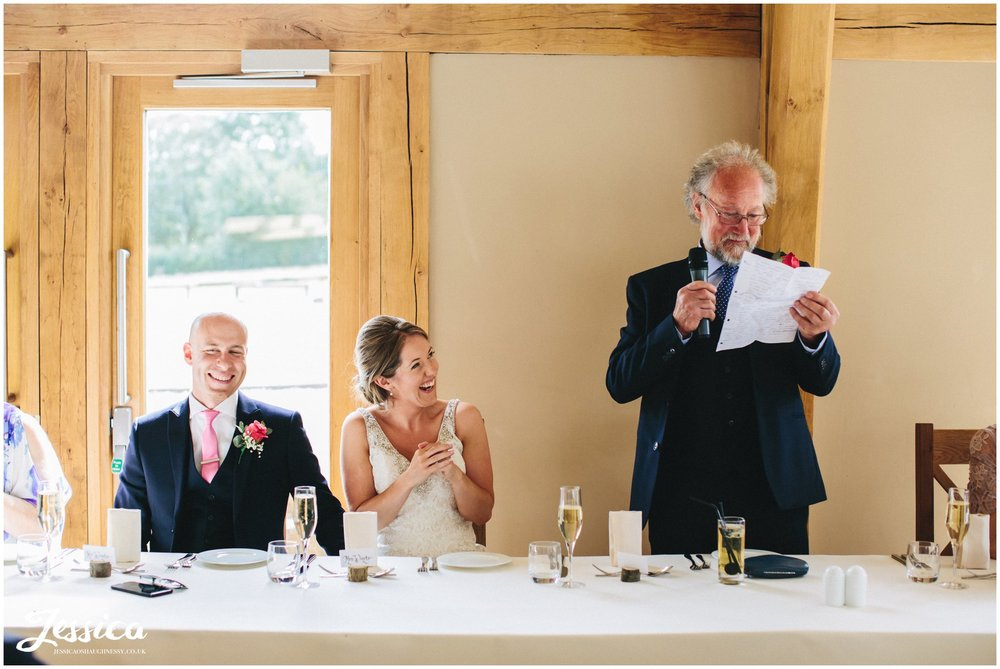 father of the bride stands and gives speech whilst the bride laughs