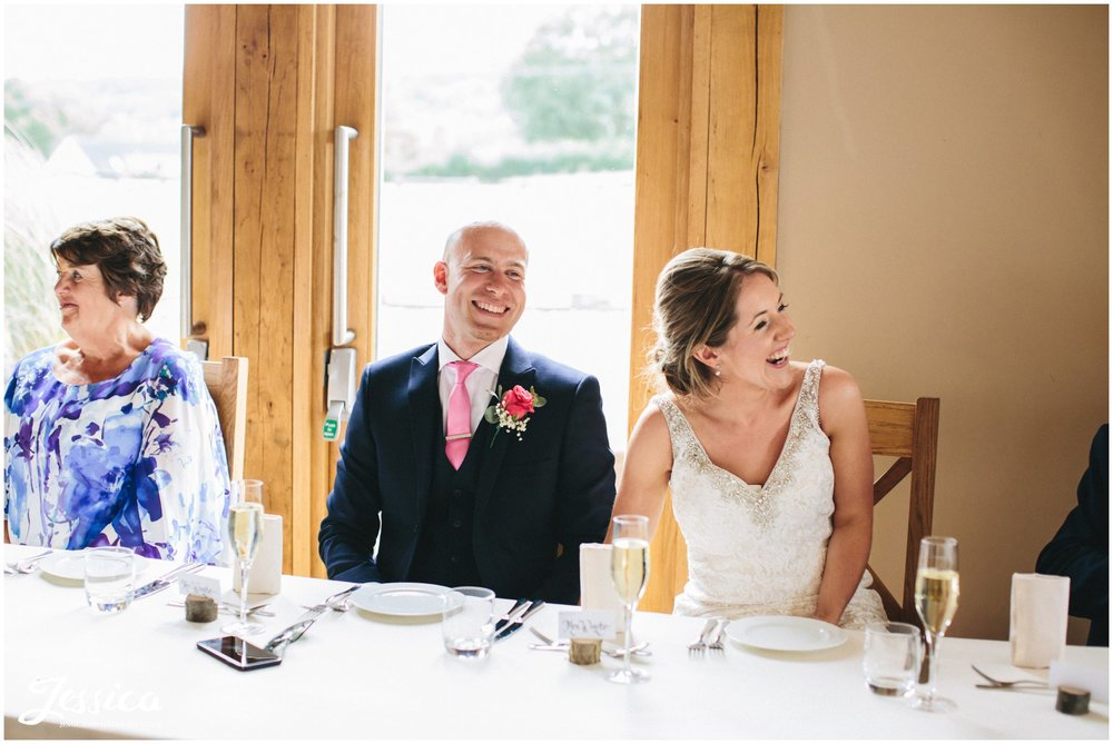 newly wed's laugh during their speeches at tower hill barns wedding venue