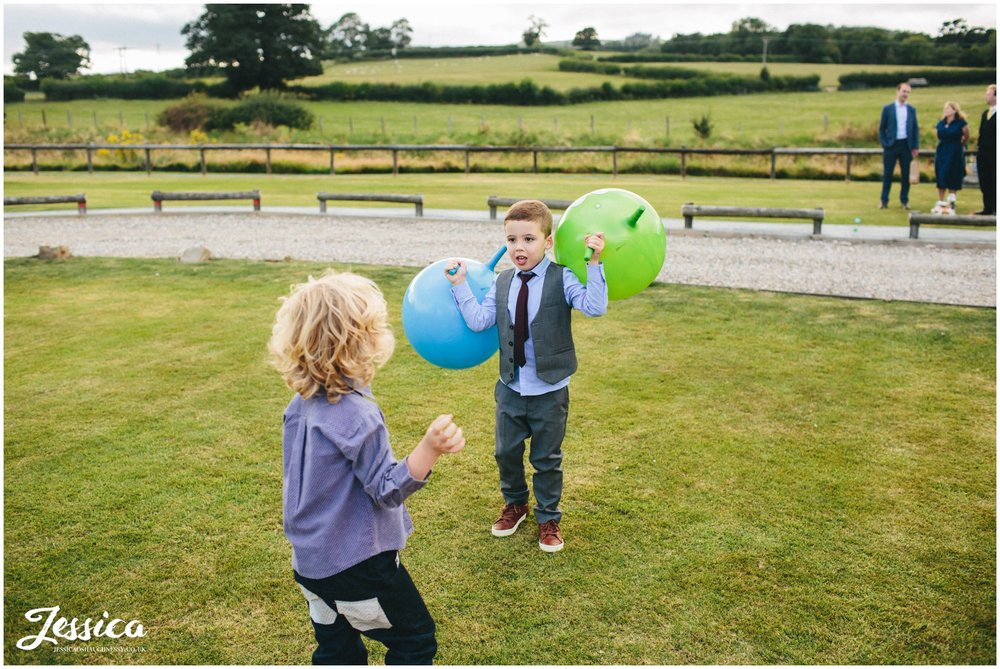 children playing with space hoppers on the grass at a north wales wedding