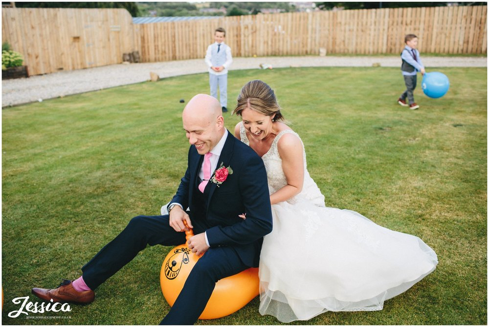 bride & groom bounce on a space hopper on their wedding day