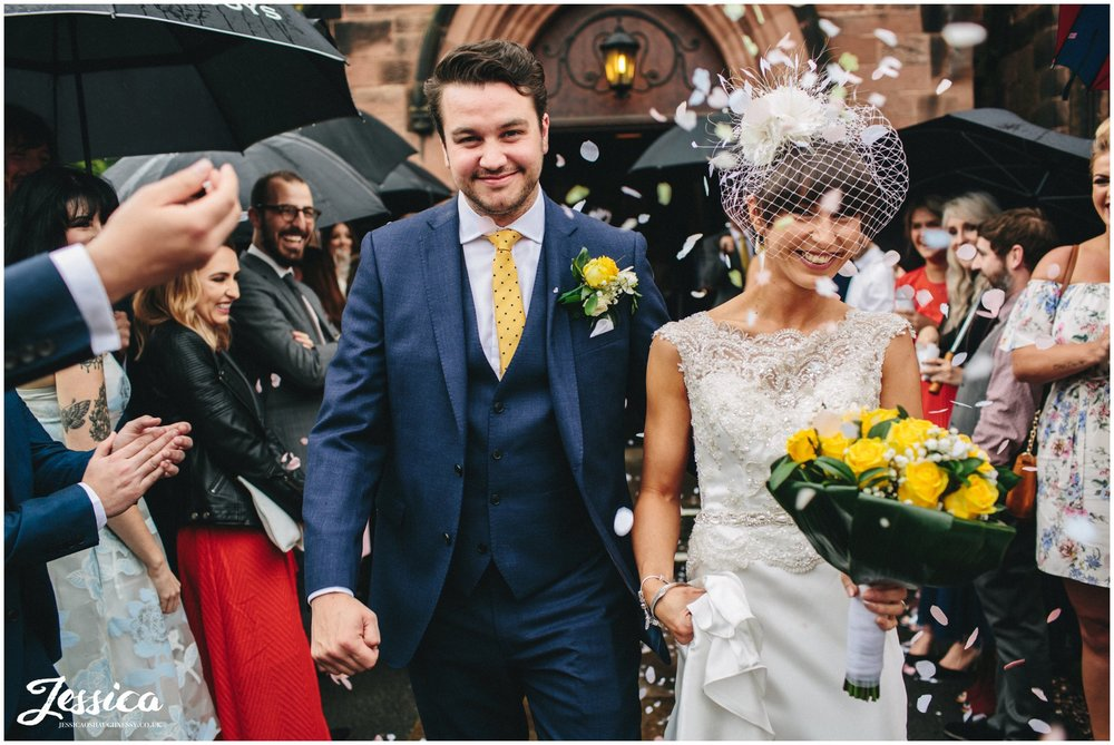 bride & groom walking through confetti line at Chester Church after their wedding