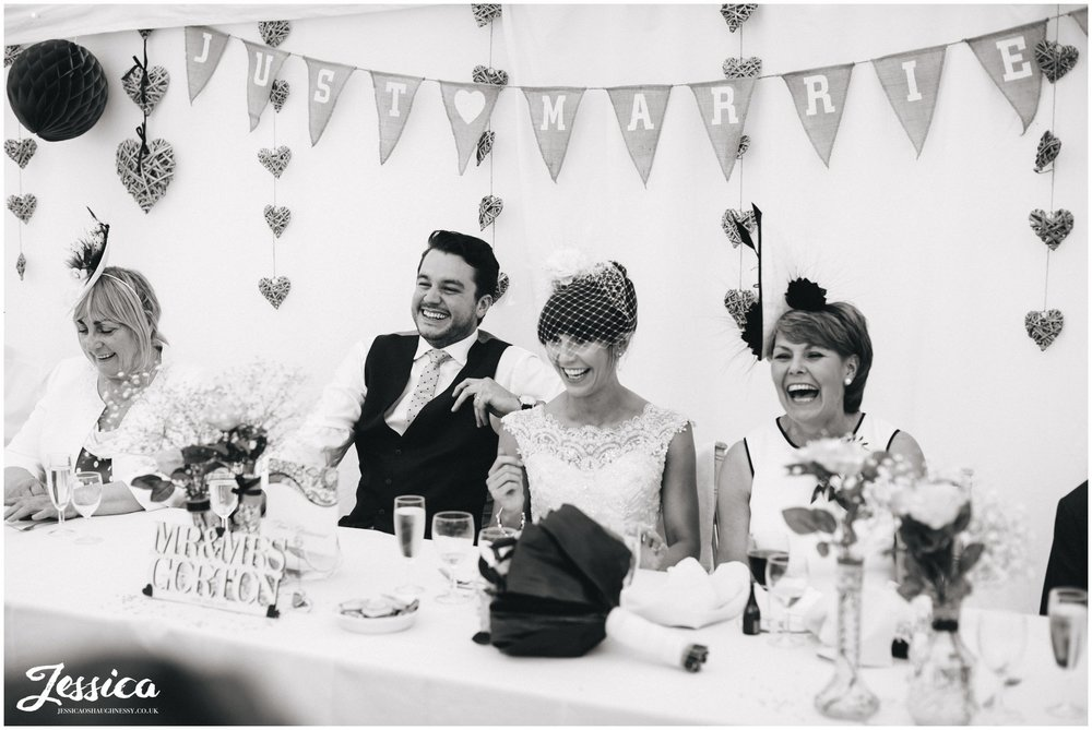 top table laugh during the speeches at a wedding in trafford hall - chester wedding photographer