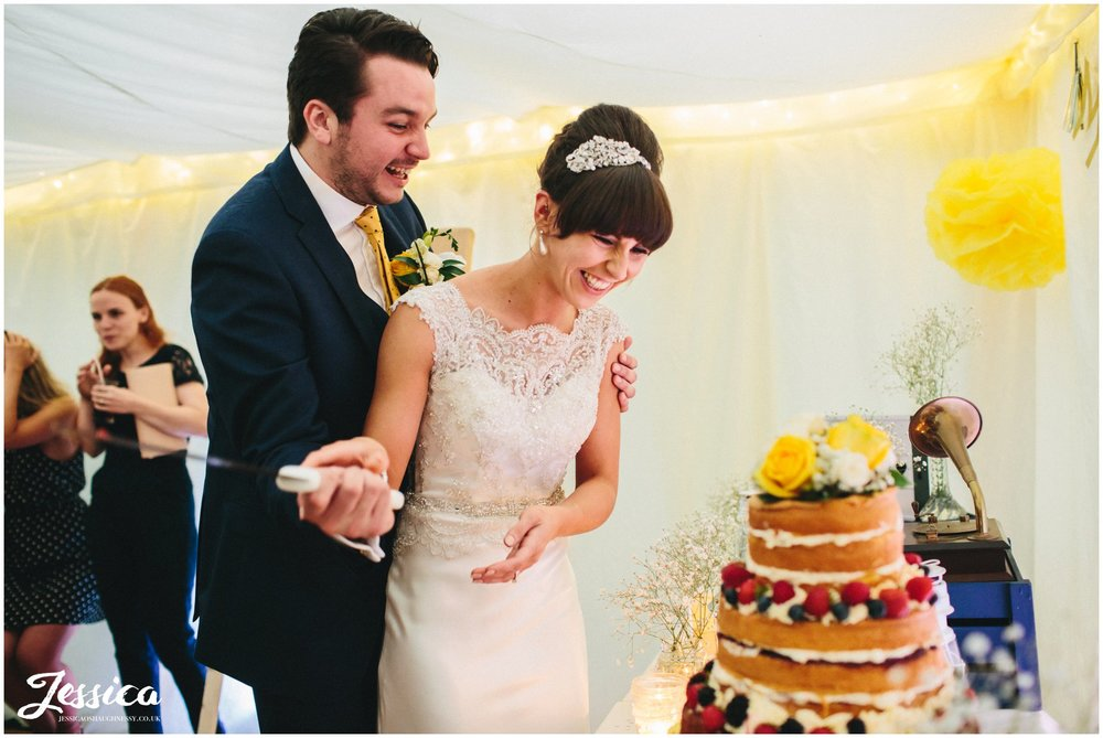 newly wed's cut the cake on their wedding day in chester