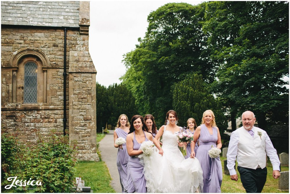 bride & bridesmaids walk up to St Bridget's Church in Bridekirk for the cumbria wedding