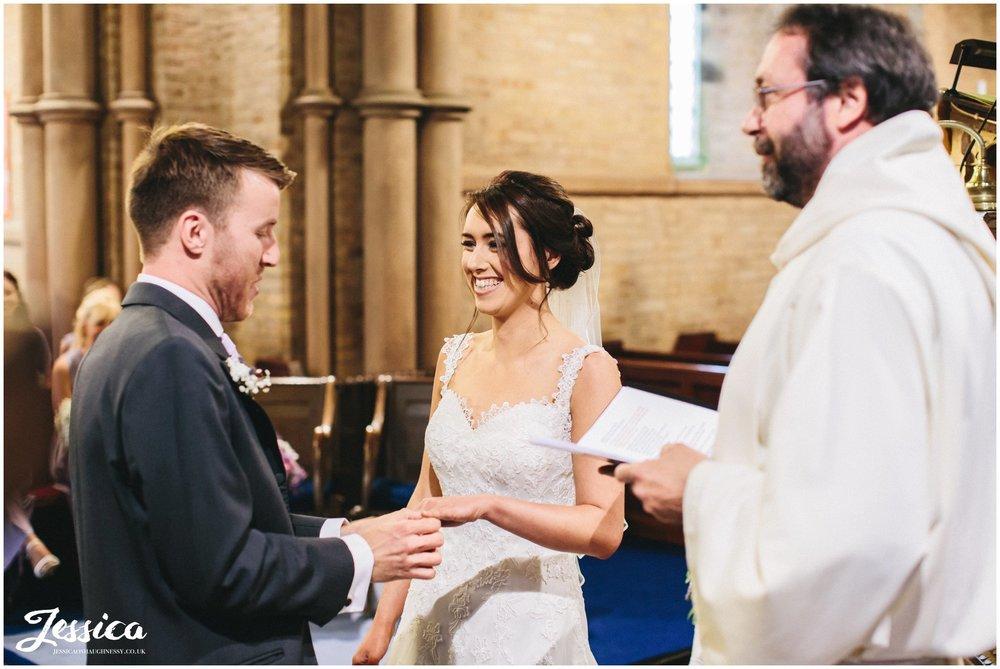 bride & groom exchange rings in St Bridget's church in Bridekirk, Cumbria wedding photographer