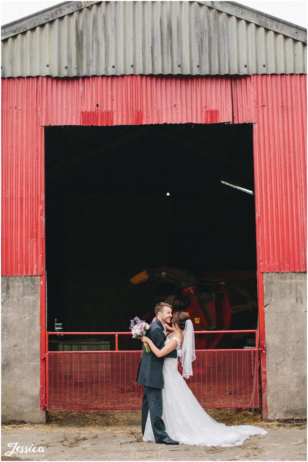 bride & groom kiss infront of farm gates at their cumbria wedding