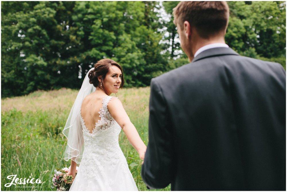 bride & groom walk through meadow on their wedding day at Three Hills Barn, Torpenhow