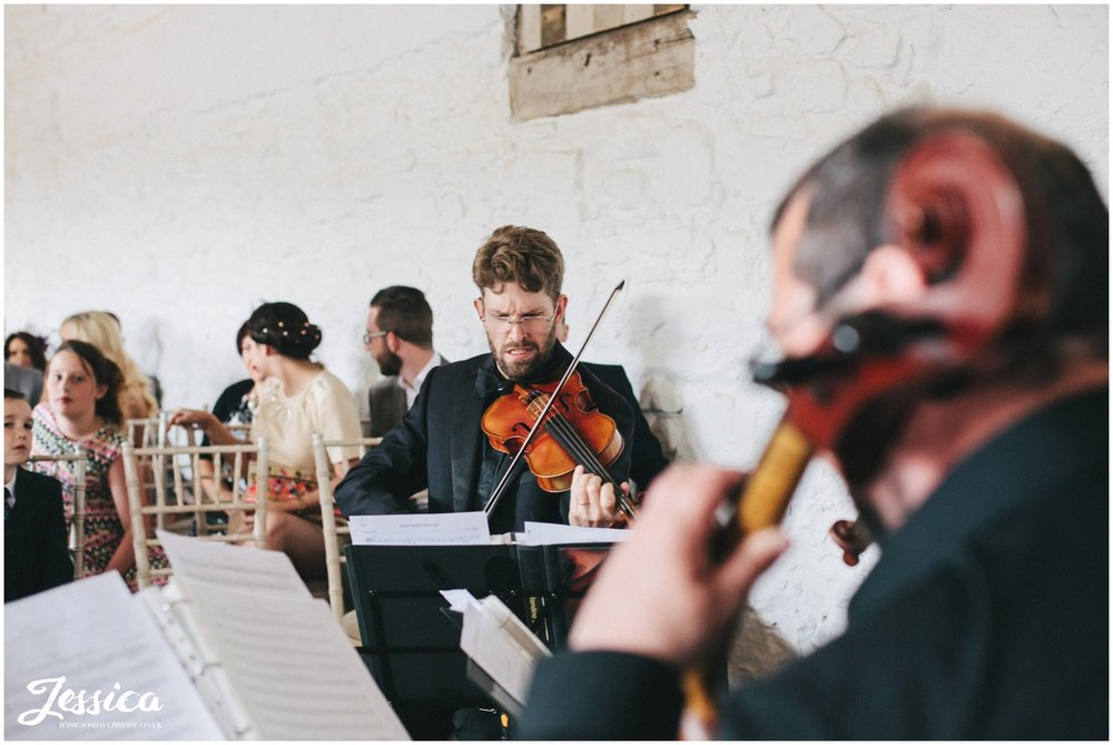 violinists play as bride walks down the aisle in bank barn, askham hall