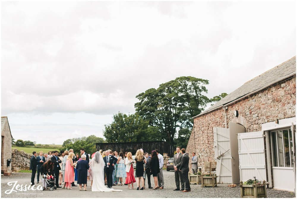 guests gather outside bank barn after the wedding at askham hall in penrith