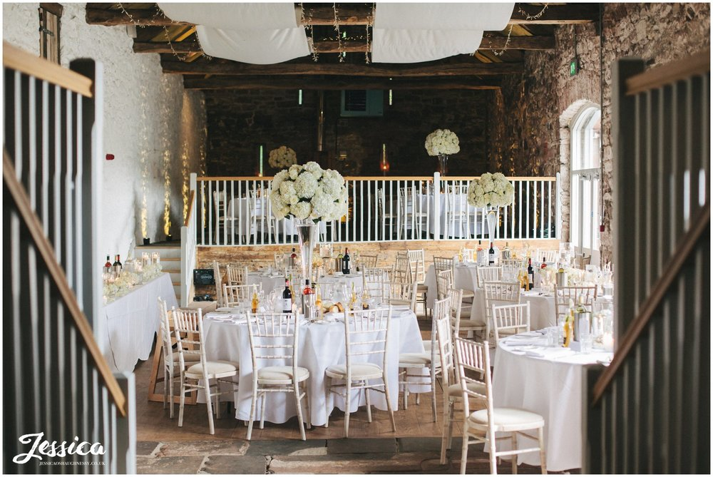 bank barn at askham hall decorated in ivory flowers ready for the wedding breakfast