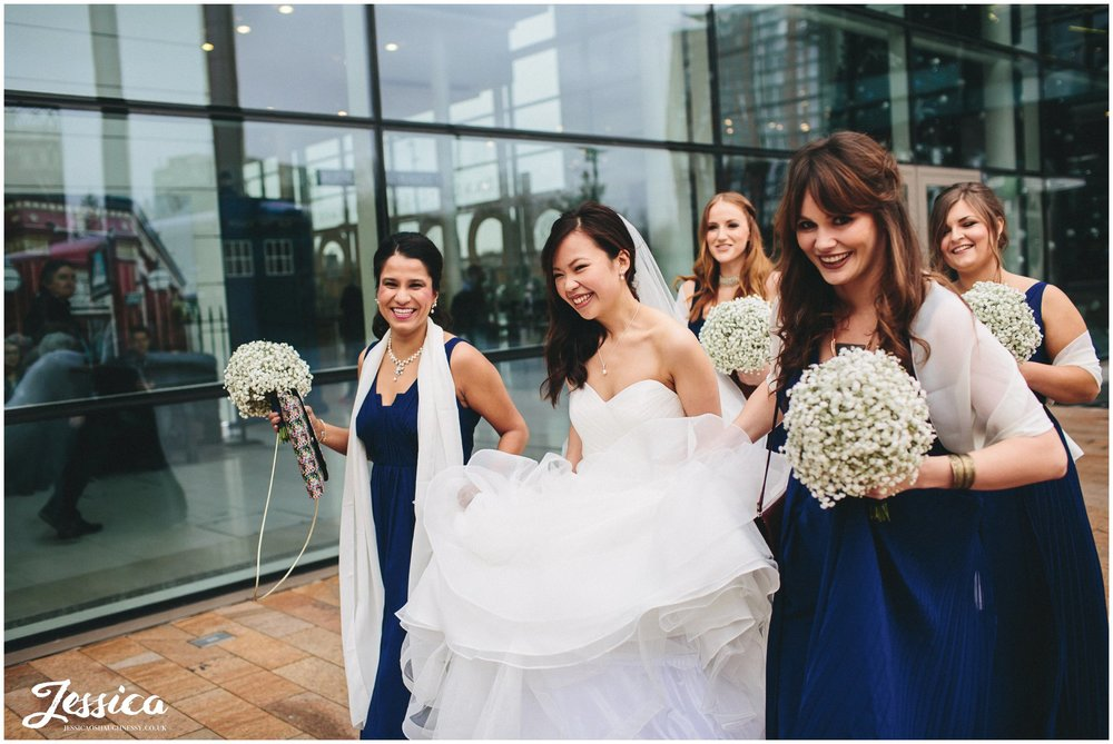 Bridesmaids carry brides dress as she walks through Media City in Manchester to her wedding at On The 7th