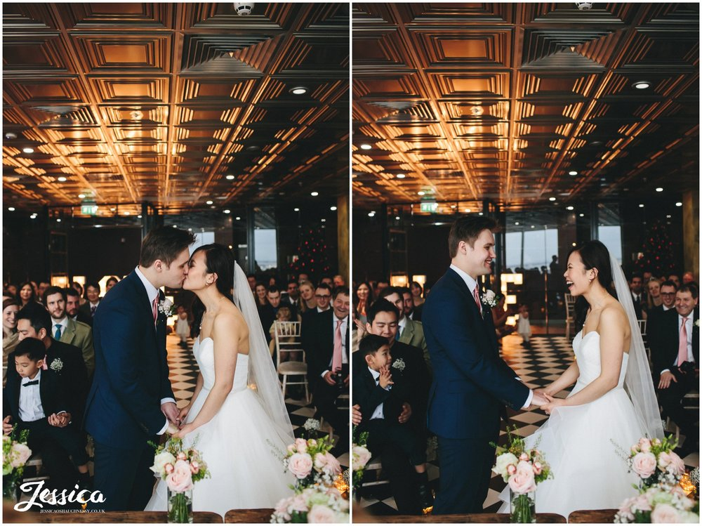 newly wed's share their first kiss during their wedding ceremony at on the 7th - media city, manchester