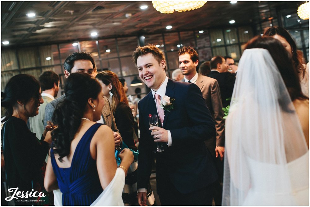 groom laughs with guests after his wedding ceremony in manchester