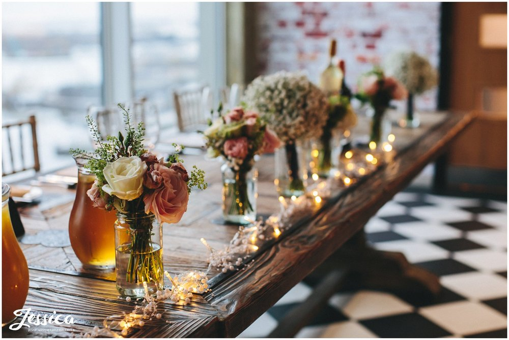flowers in jars decorate the top table - On The 7th Wedding