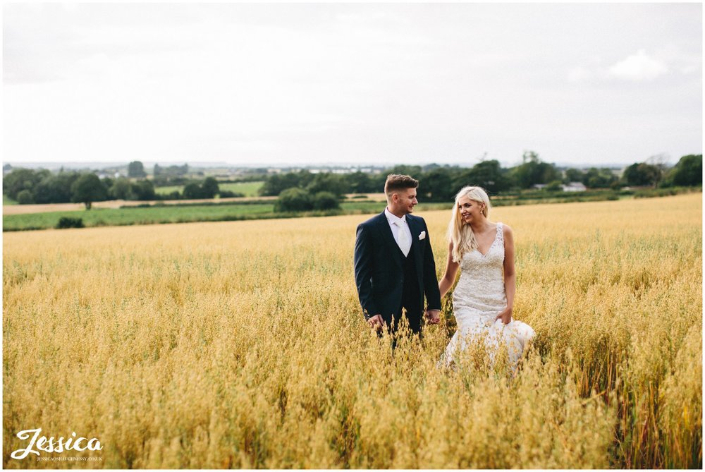 bride & groom walk through golden corn fields at their lancashire wedding