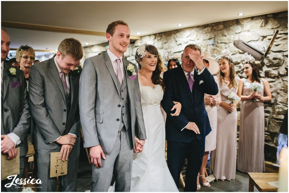 bride & groom laugh during their north wales wedding ceremony