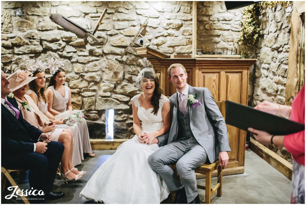 couple sit during their wedding ceremony at tower hill barns