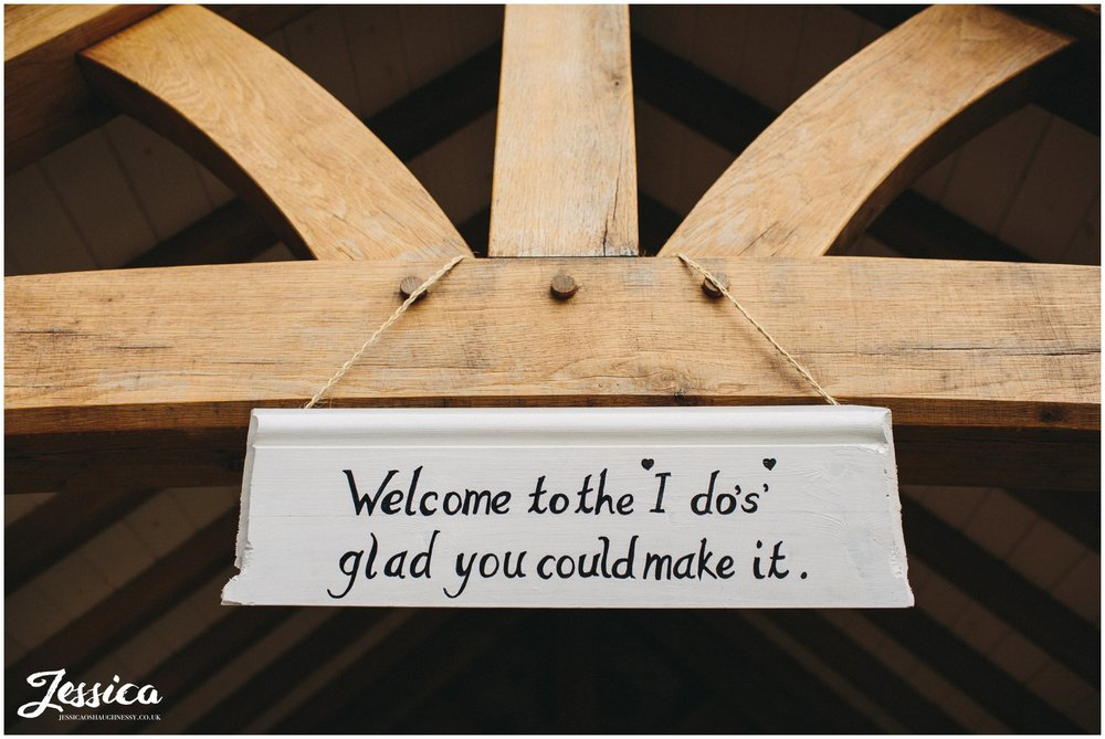 sign at the entrance to tower hill barns wedding venue, welcoming guests into the ceremony