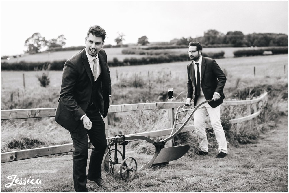 guests joke with farming equipment at tower hill barns wedding venue