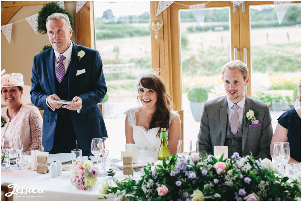 bride laughs during the father of the bride's speech in barn