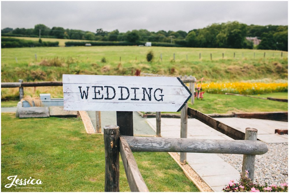 sign saying wedding points guests in the right direction
