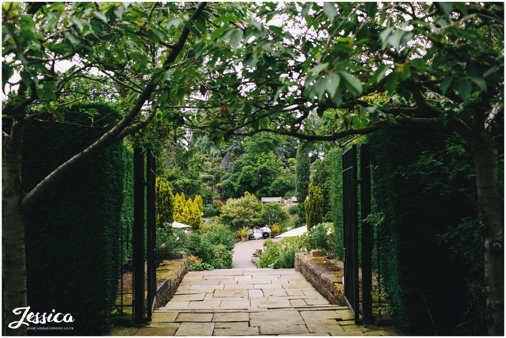 a view through the gates of ness gardens before the wedding