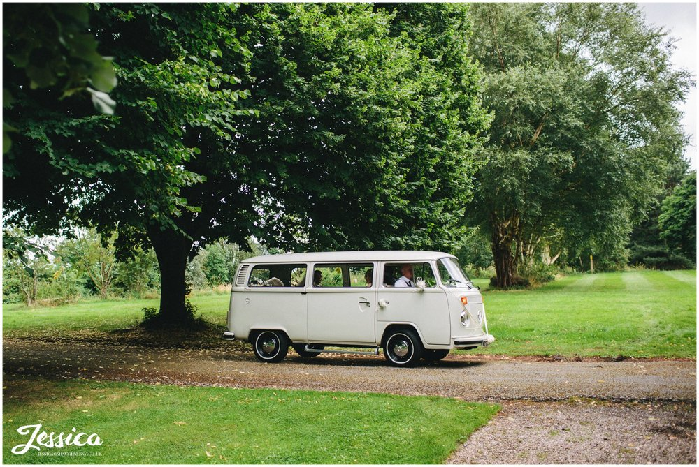 bride arrives at her ness gardens wedding in a cream VW camper van