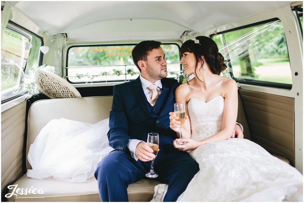 newly wed couple sip champagne in a VW camper at their ness gardens wedding