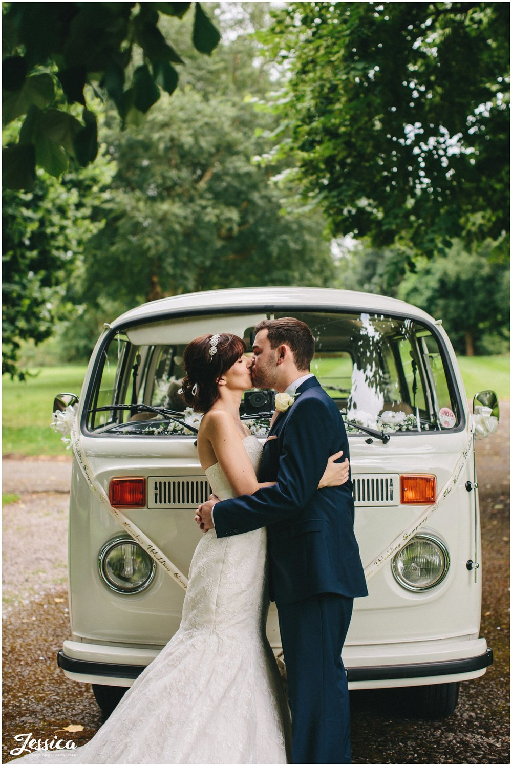 bride & groom share a kiss in ness gardens in front of their VW Camper on their wedding day