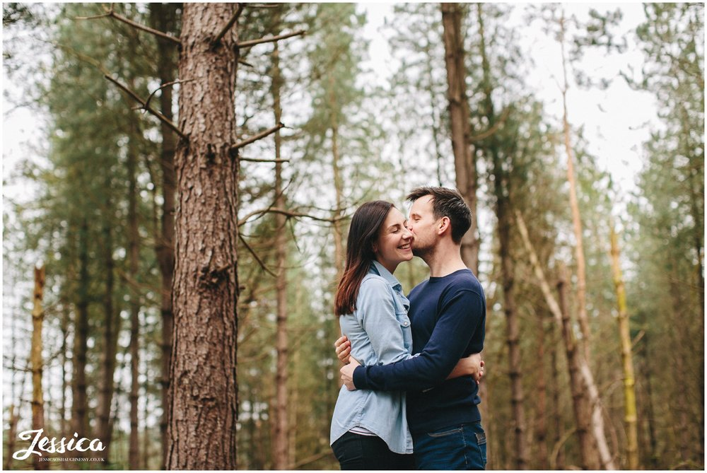 couple embrace surrounded by trees in delamere forest - cheshire wedding photography