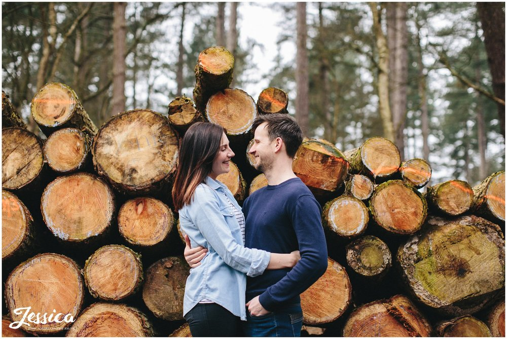 couple stand in front of chopped down trees - cheshire wedding photographer