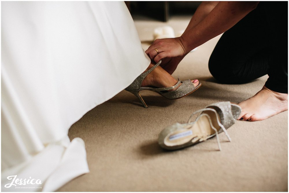 bridemaid slips on brides shoes for her on the morning of her wirral wedding