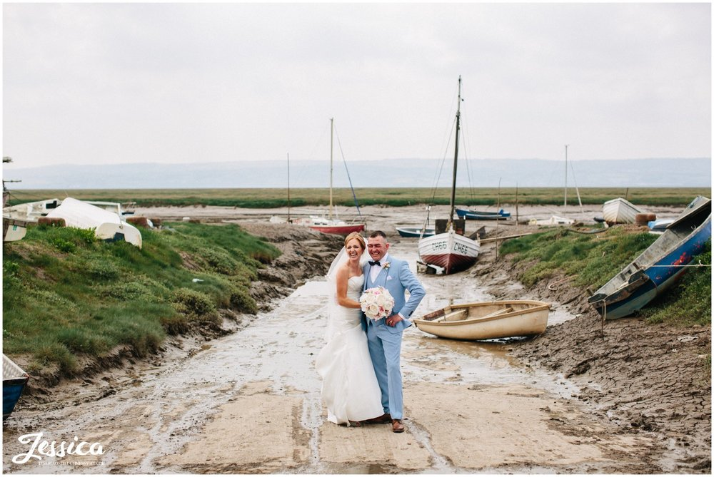 newly wed's stand between boats on the waterfront at their wedding at sheldrakes