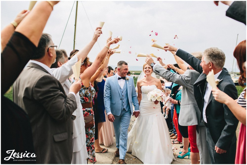couple walk through the confetti line at their wirral wedding