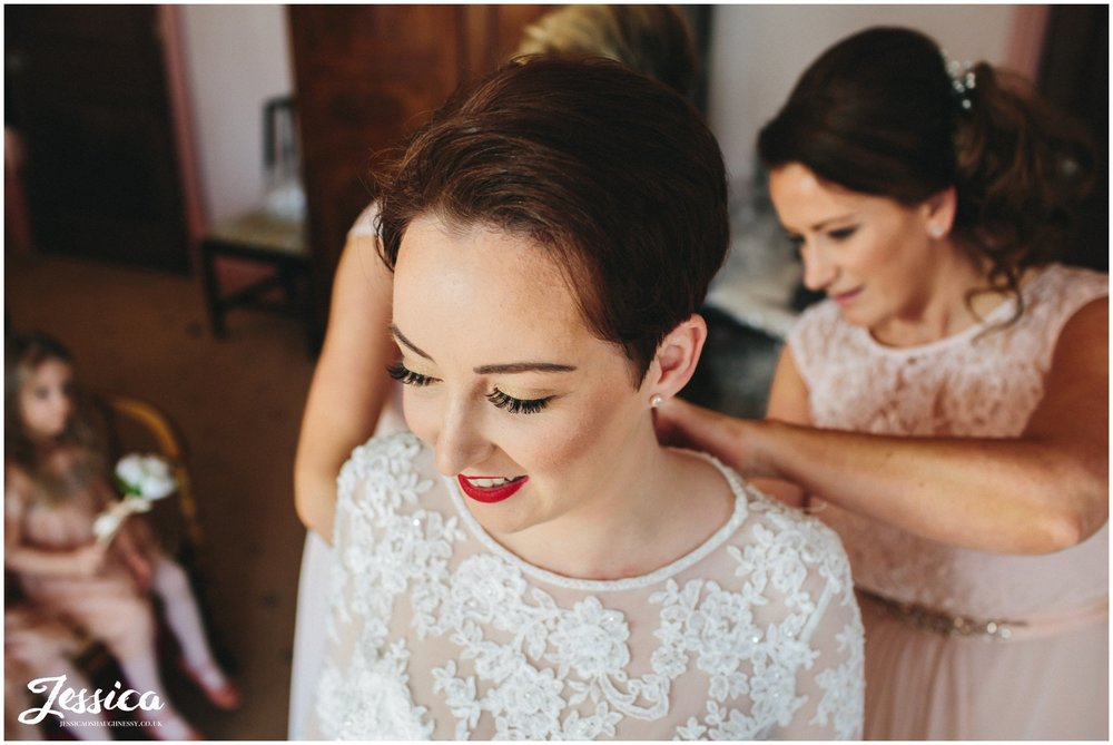 the bride is helped into her wedding dress by her bridesmaids - wirral wedding photographer